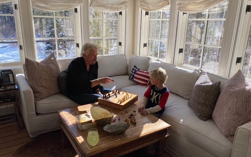 Richard Branson sitting on a sofa playing chess with his young grandson