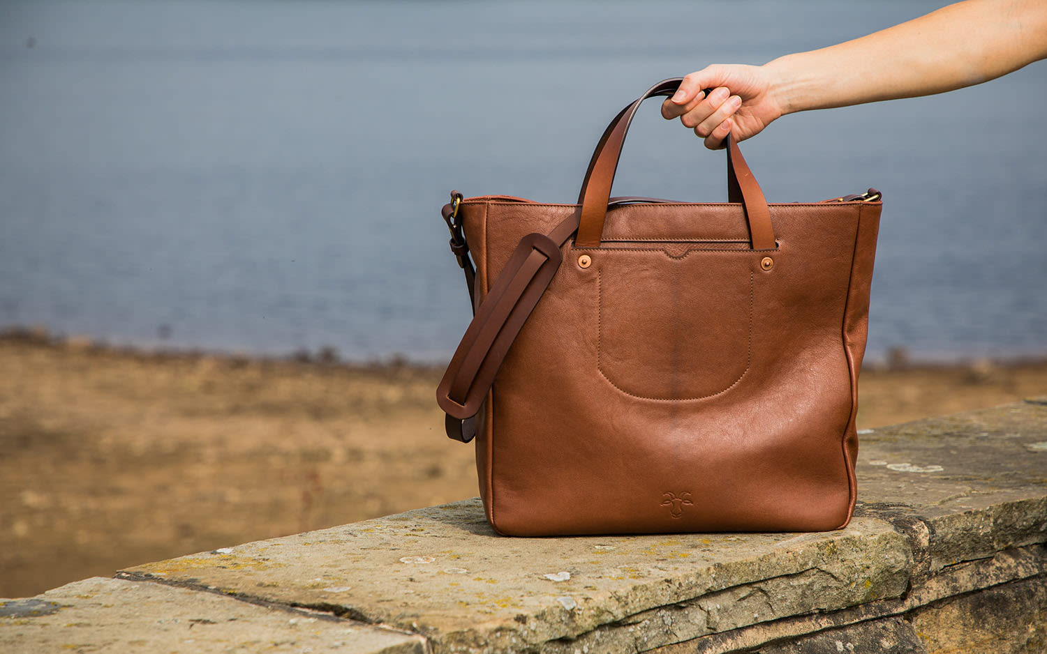 A brown handbag on a wall with a person's arm picking it up