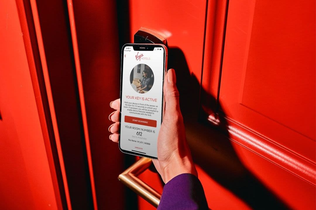 A hand holding an iPhone showing the Virgin Hotels app opening a red hotel room door