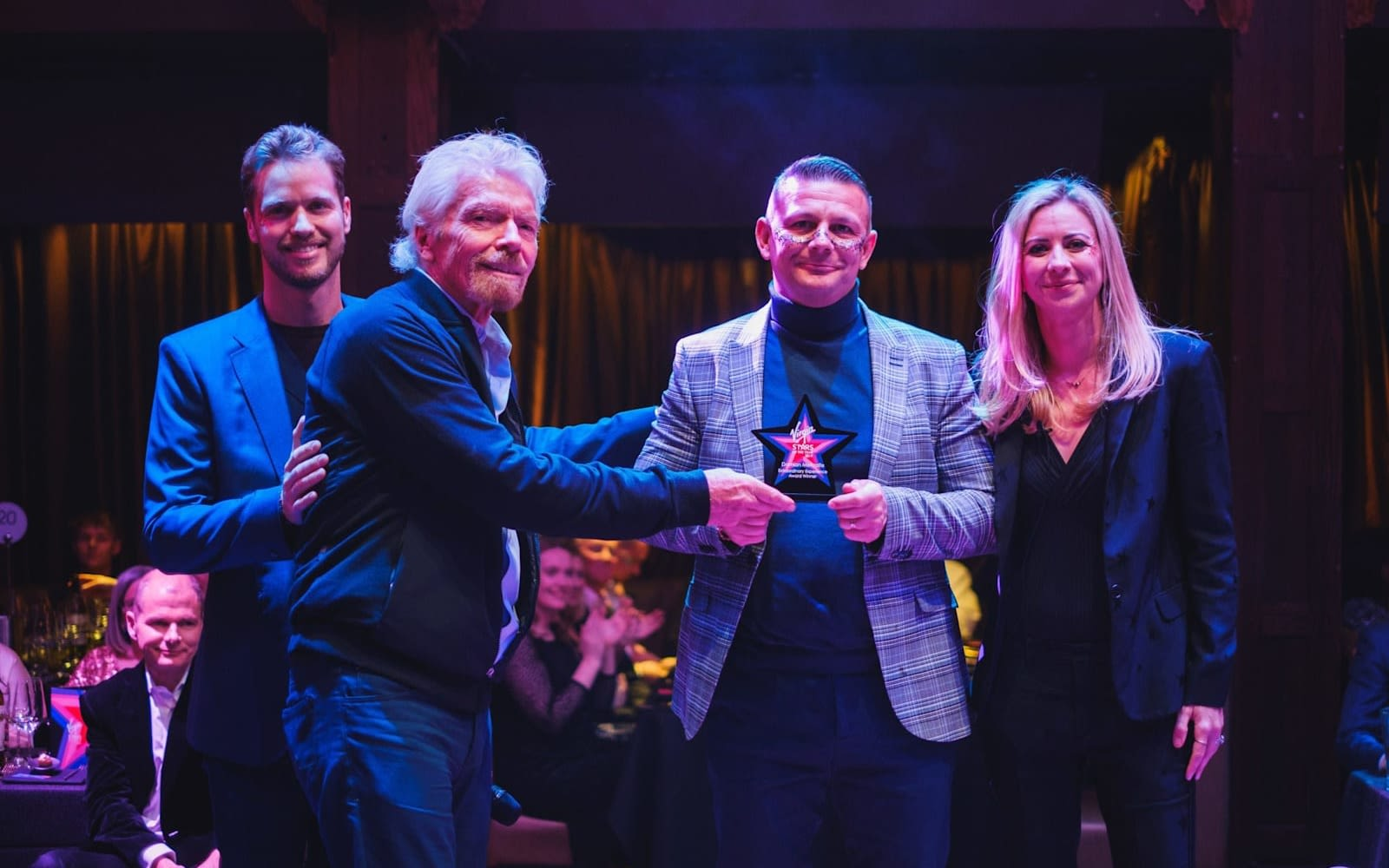 Richard, Sam and Holly Branson on stage presenting an award to Damien Metcalfe