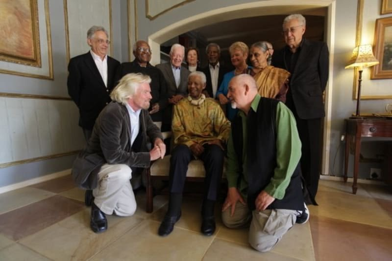Richard Branson and Peter Gabriel kneel next to Nelson Mandela - surrounded by The Elders