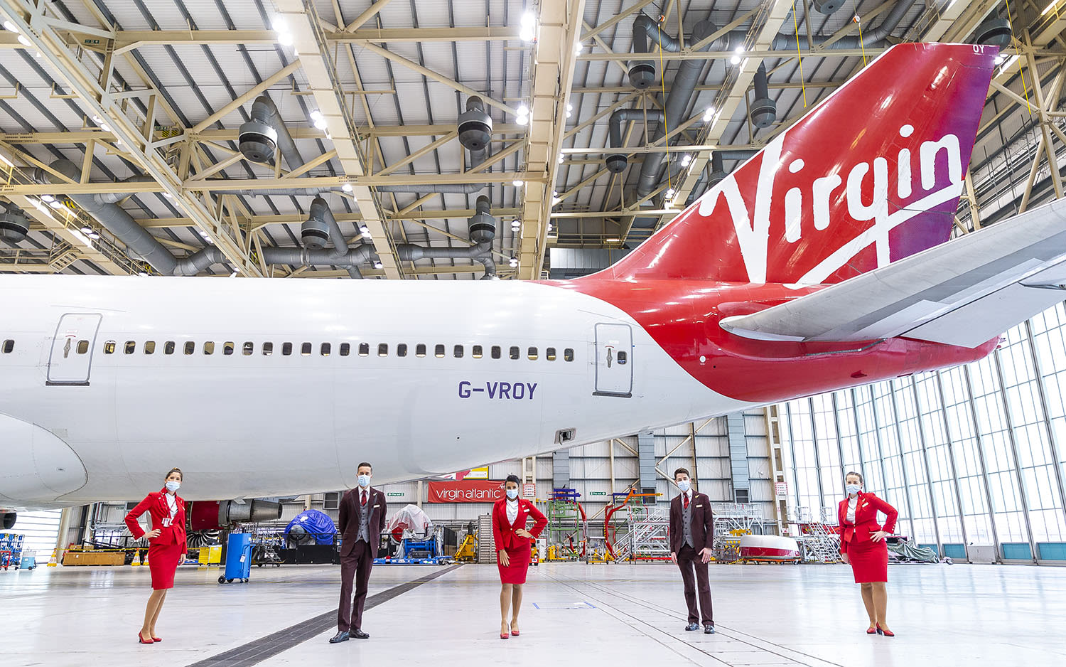 Five cabin crew stand in an aircraft hangar next to Virgin Atlantic's Boeing 747, Pretty Woman