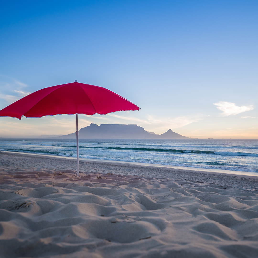 A red umbrella on a beach with Table Mountain in the background