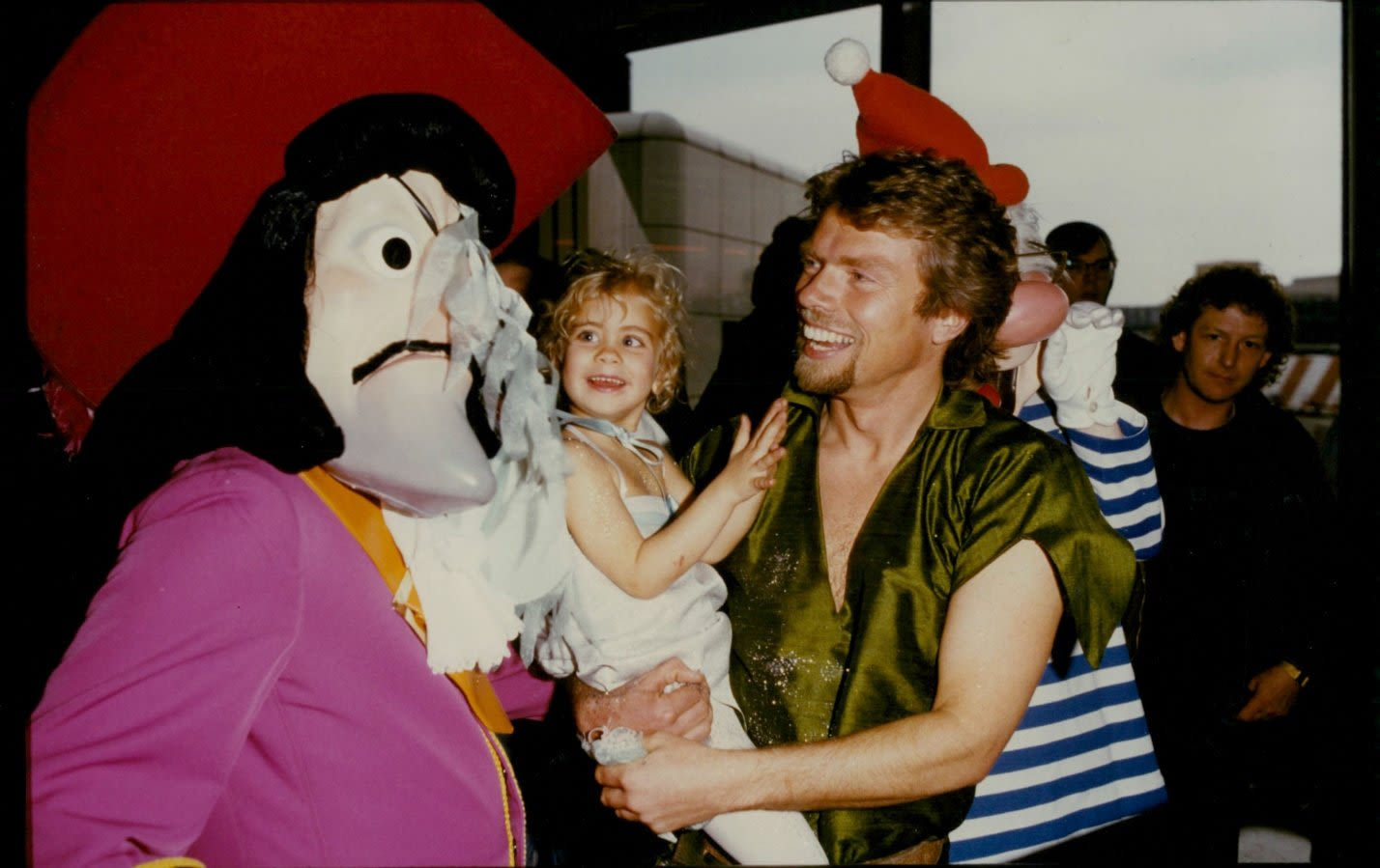 a young Richard Branson dressed as Peter Pan carries a toddler Holly Branson dressed as Tinkerbell