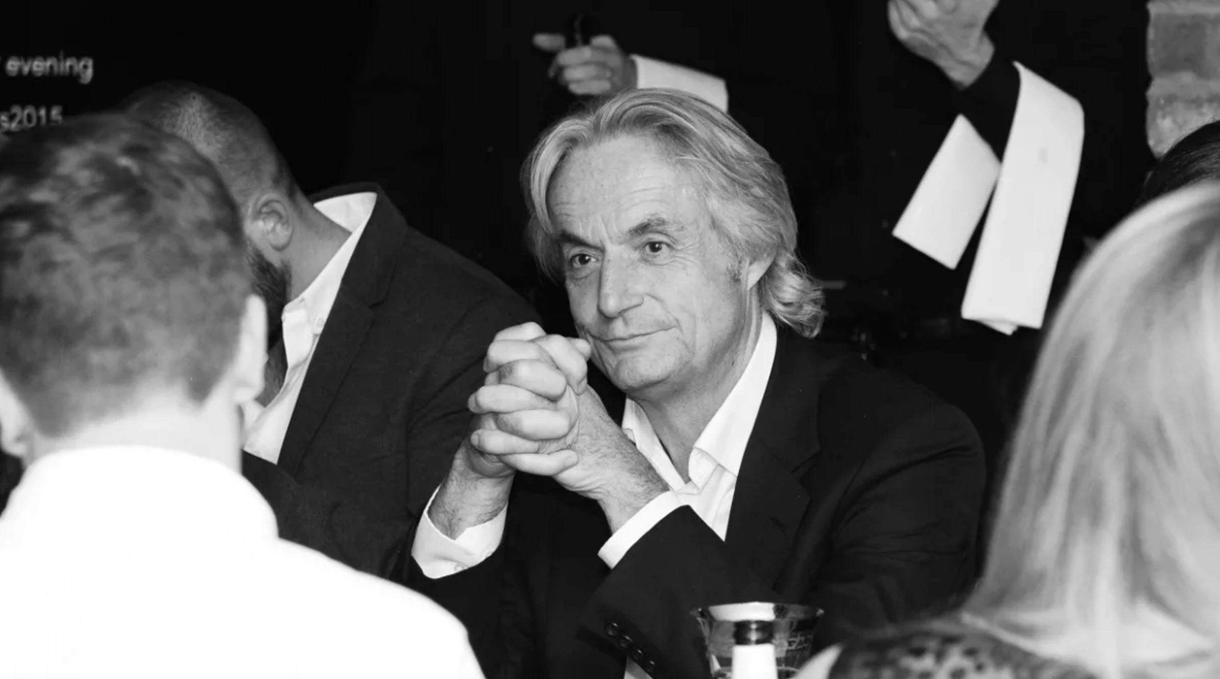 Peter Norris listening at a black tie event