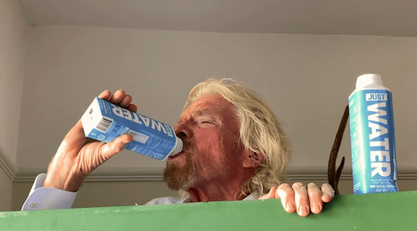 Richard Branson drinking a carton of Just Water, with another carton by his side