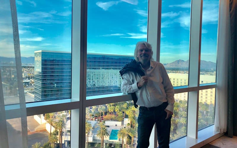 Richard Branson at the Virgin Hotel in Las Vegas standing by the window with his jumper over his left shoulder