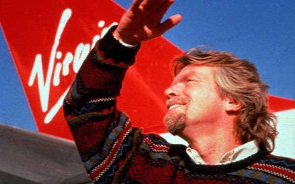 Richard Branson stands in front of a Virgin Atlantic plane