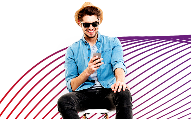 A man wearing a hat and sunglasses, sitting on a chair using his phone