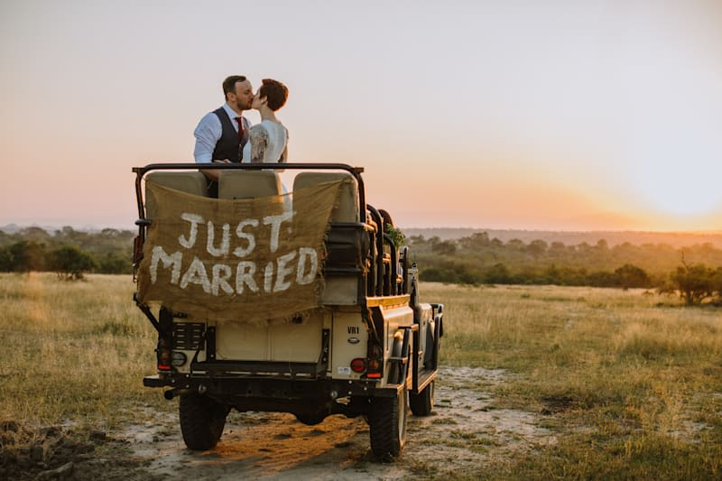 A couple kiss in a safari jeep with a Just Married sign on the back of it