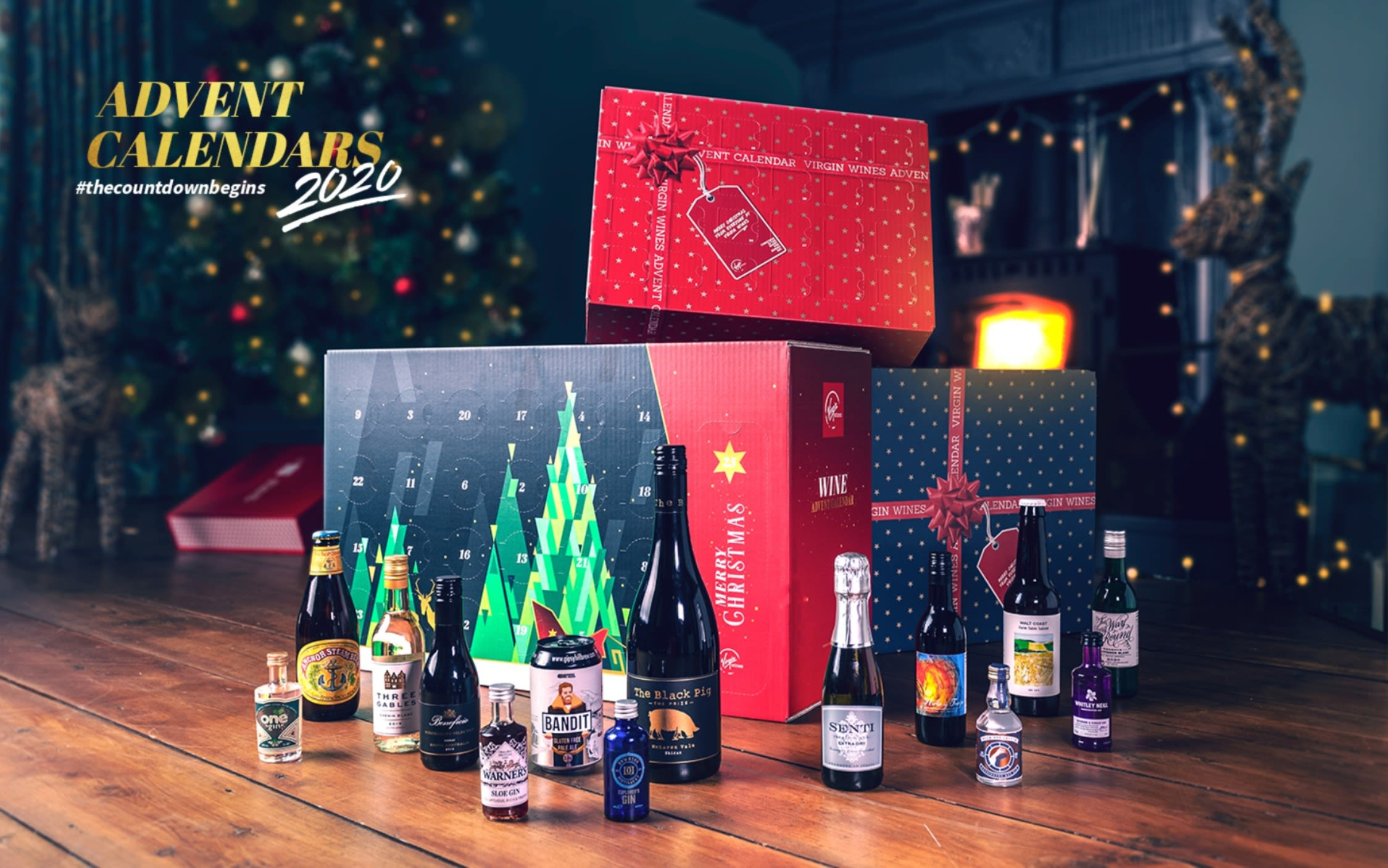 A Virgin Wines advent calendar with four small bottles of wine and two Christmas soft toys on a kitchen counter