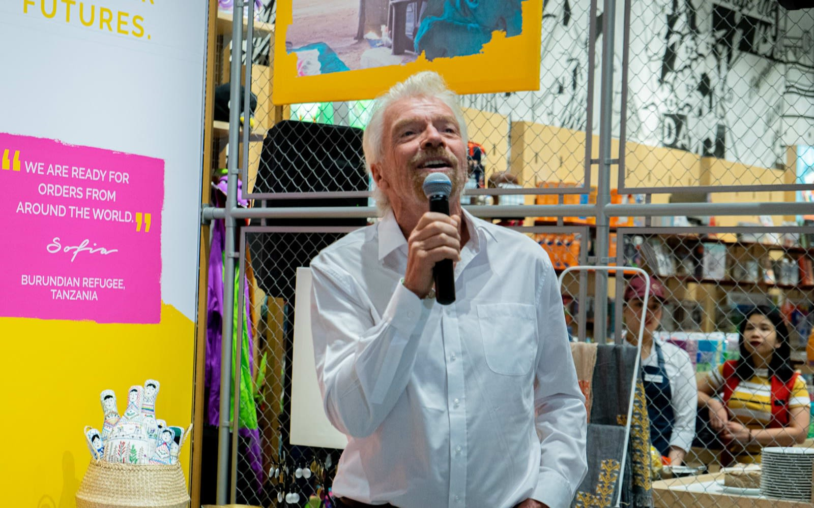 Richard Branson in white shirt holding a microphone and smiling