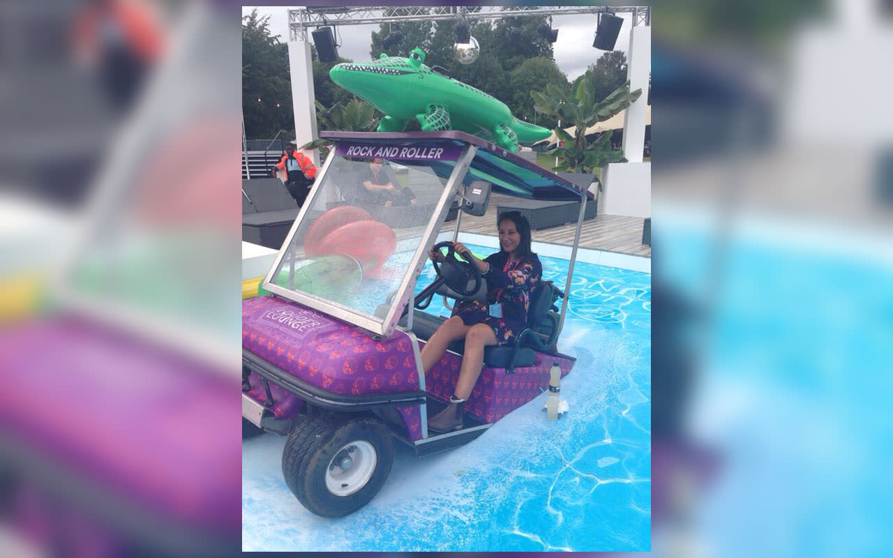 Charmaine Clarke posing in a golf buggy on water with an inflatable crocodile on the roof at V Festival
