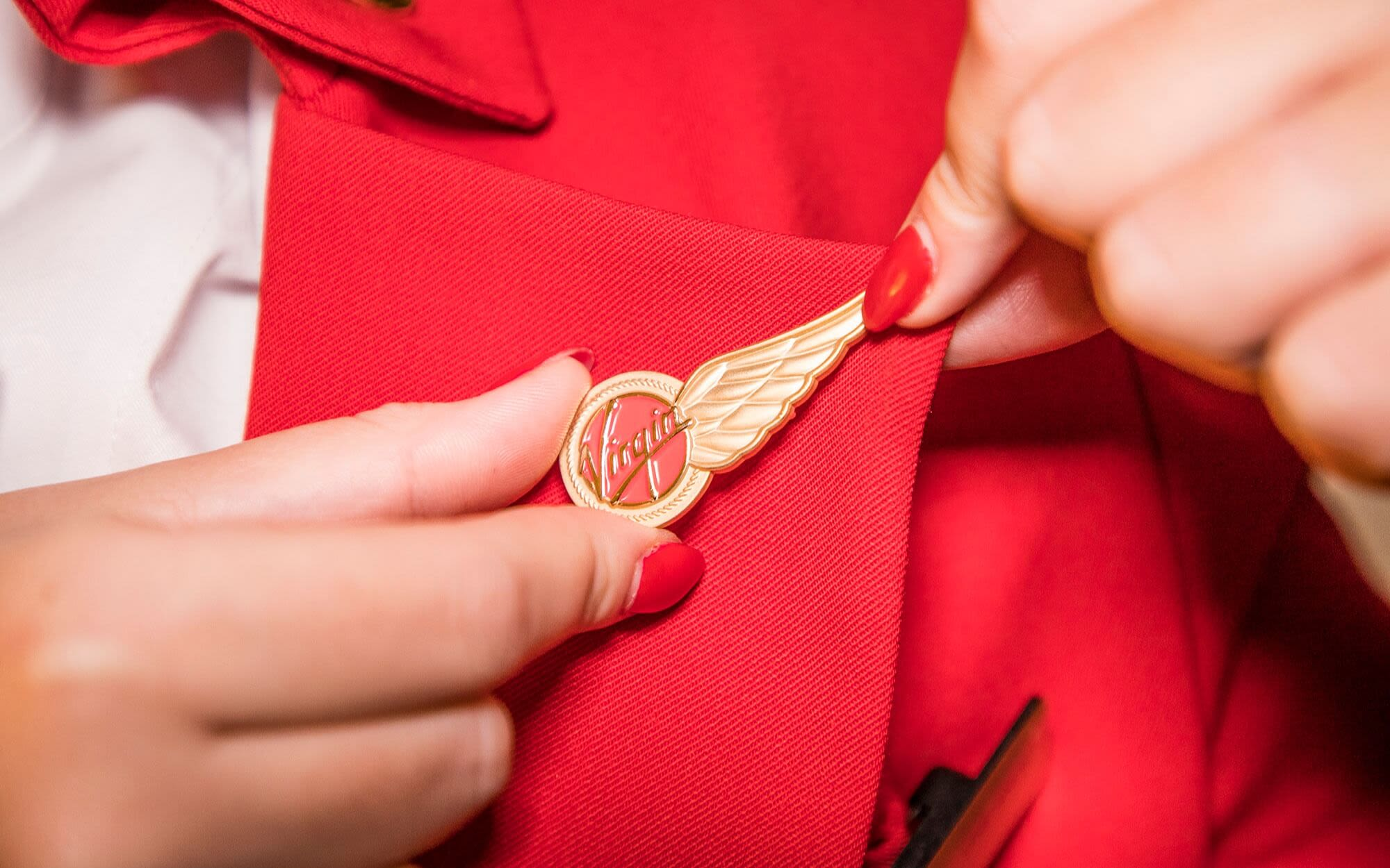 A close up of the Virgin Atlantic wings pin on a lapel. The wearer is adjusting it