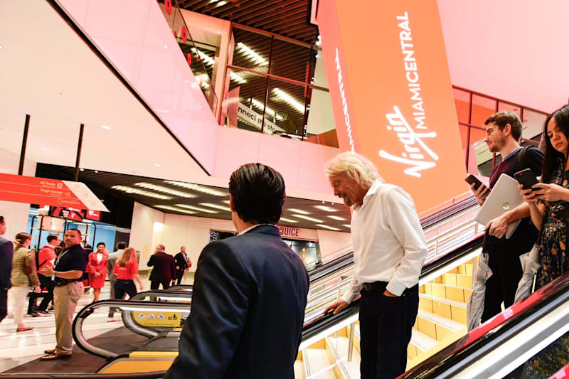 Richard Branson travelling down an escalator at Virgin Trains Miami Central station