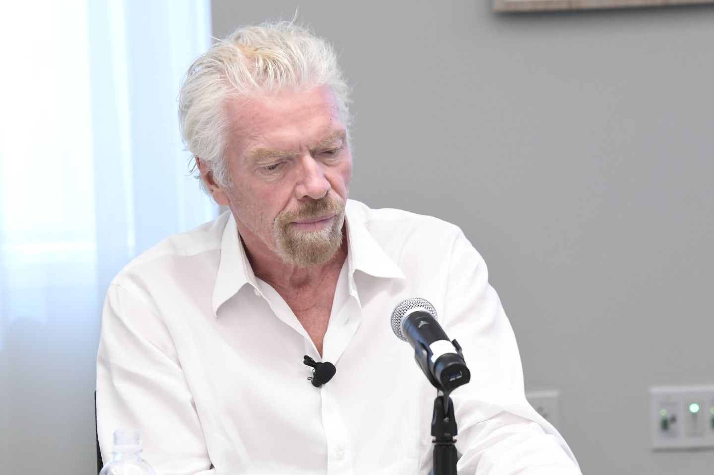 Richard Branson wearing a white shirt at a panel discussion