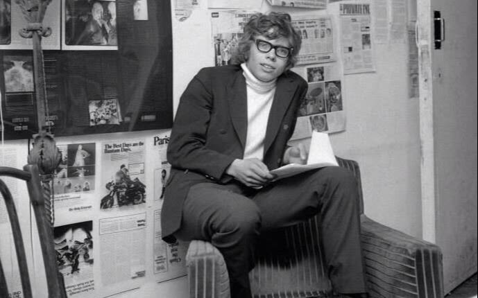 Black and white image.  Richard Branson as a student. He wears thick rimmed glasses and a turtle neck top with a jacket