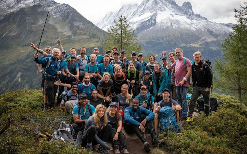 Richard Branson with a team of hikers with mountains behind them