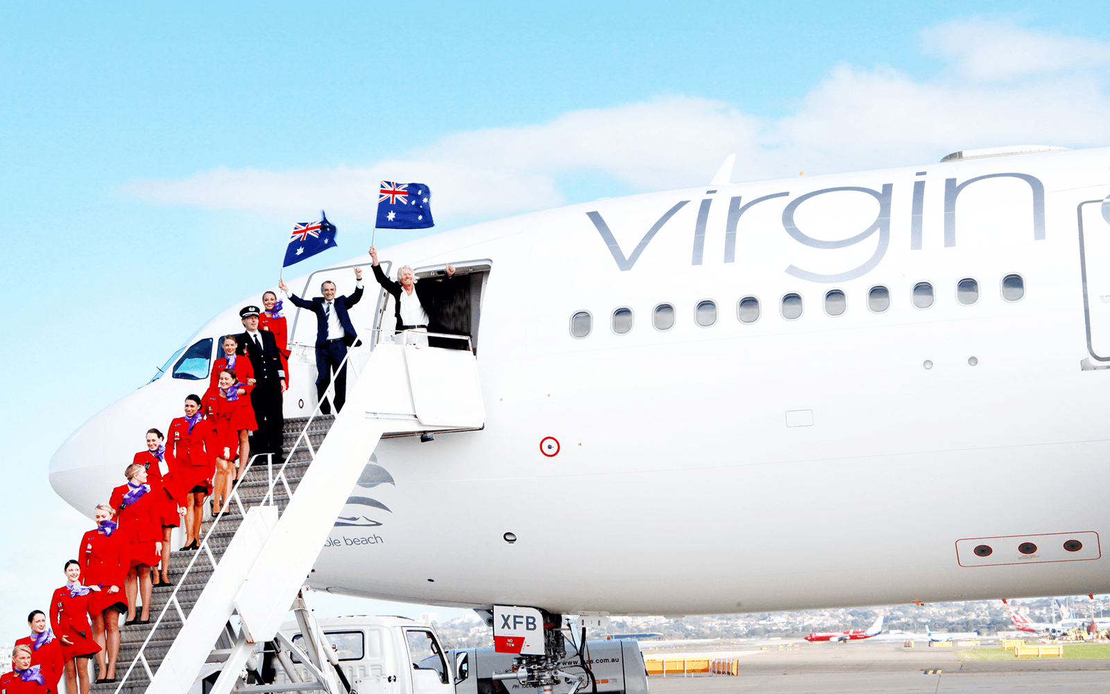 Richard Branson and Virgin Australia employees fly the Australian flag on the steps of a Virgin Australia aeroplane