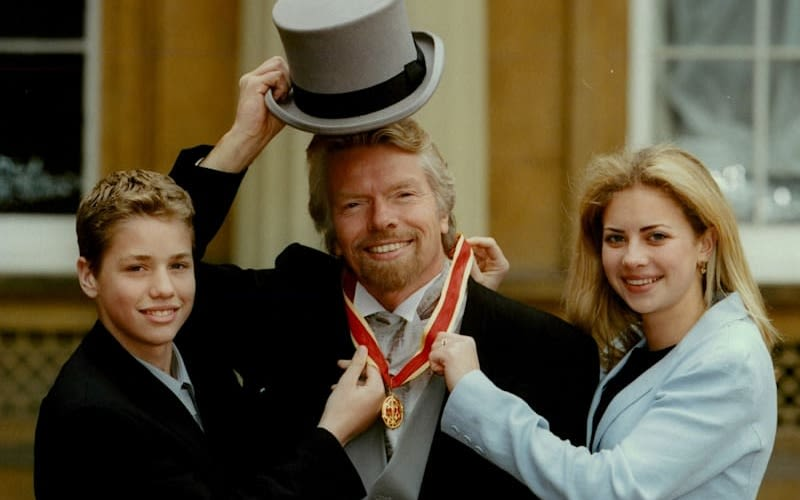 Richard Branson stands between his son and daughter who are smiling and holding his medal