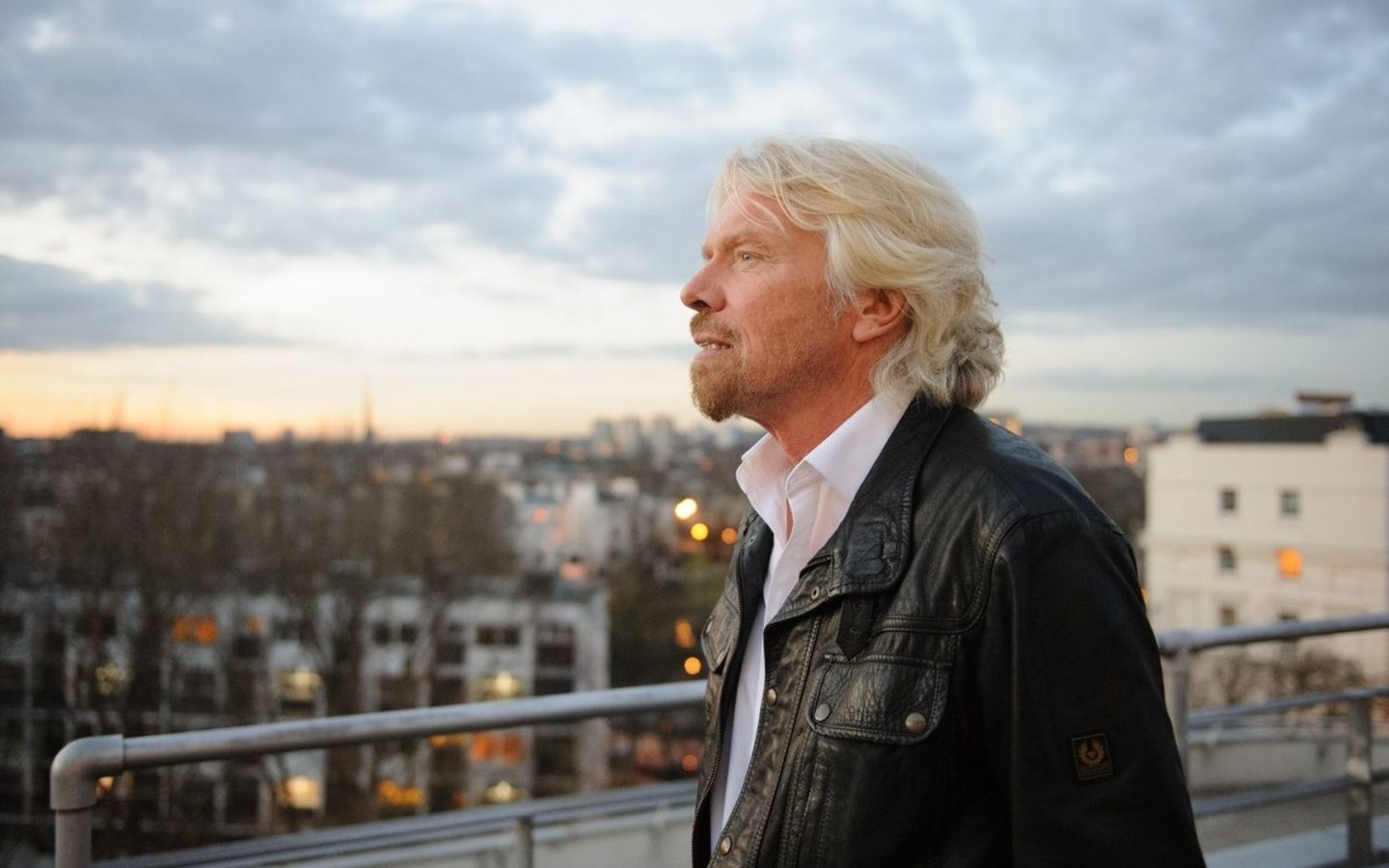 Richard Branson on the rooftop of the Battleship building looking into the distance