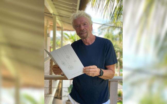 Richard Branson holding an Advent of Change calendar