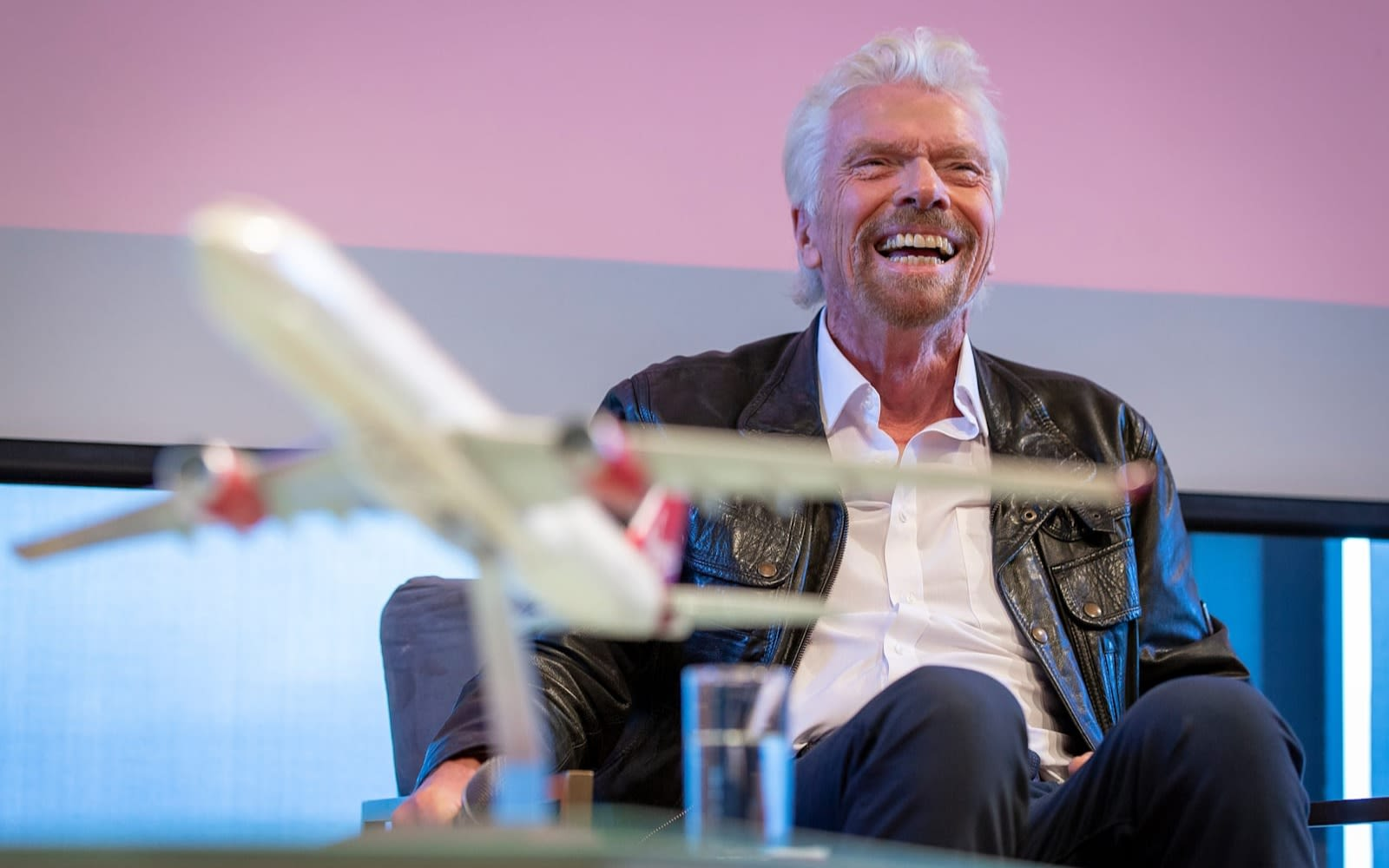 Richard Branson smiling with a model aeroplane in the foreground