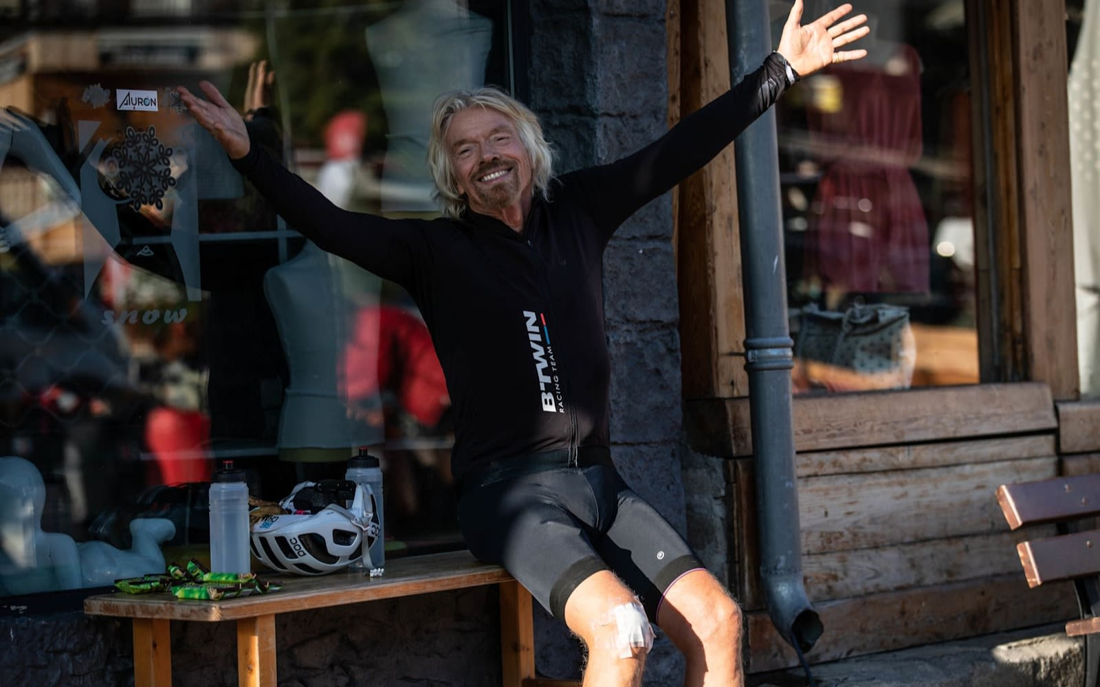 Richard Branson smiling with his arms in the air in cycling clothes