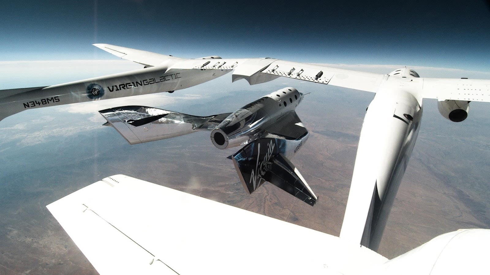 Virgin Galactic high in the sky above vast land