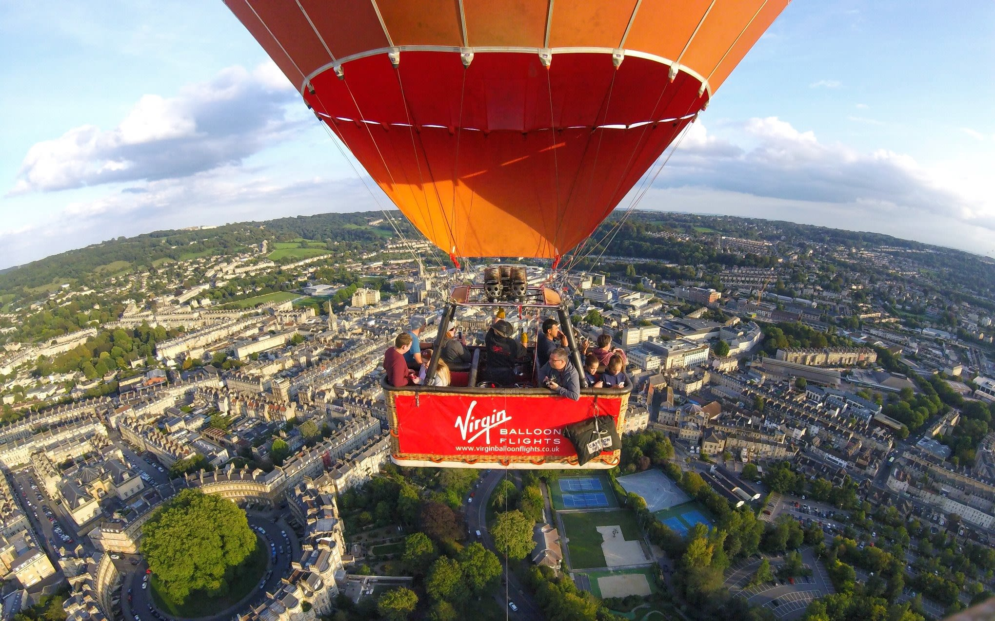A red Virgin Balloon Flights hot air balloon flies over a city
