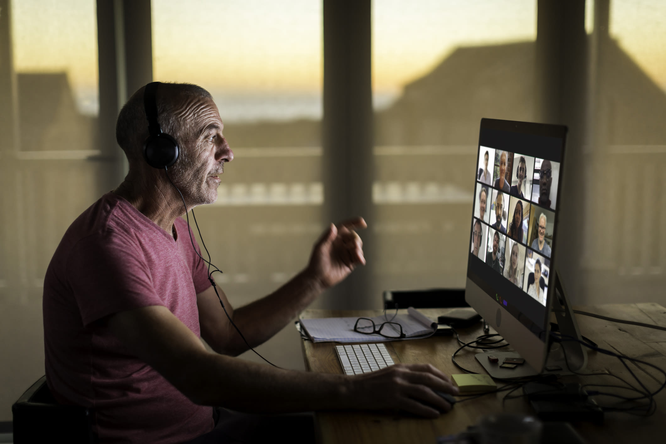 Man wearing headphones on a video call with a team of people