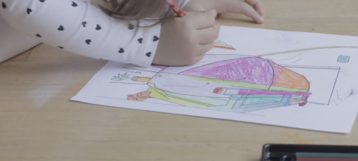 A young girl colours in a colouring page of a Virgin Hyperloop vehicle