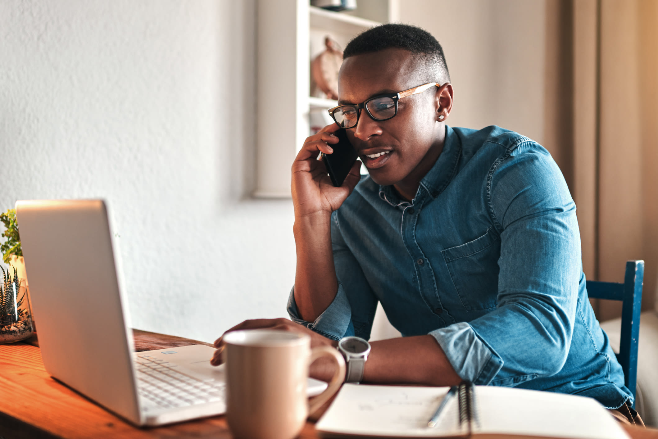 A man working from home, talking on the phone and looking at a laptop