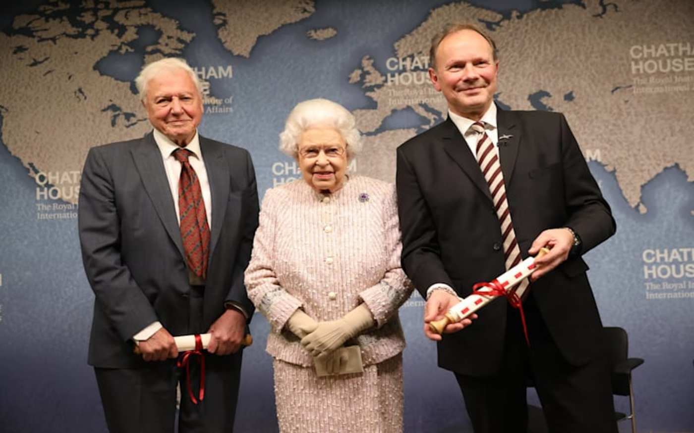 David Attenborough, the Queen and another gentleman stood in front of a large map