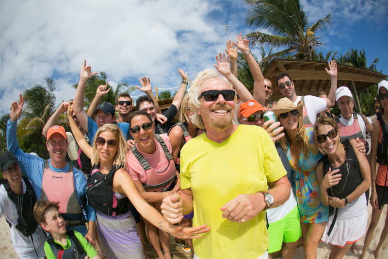 Richard Branson smiling in front of a group of people on Necker Island