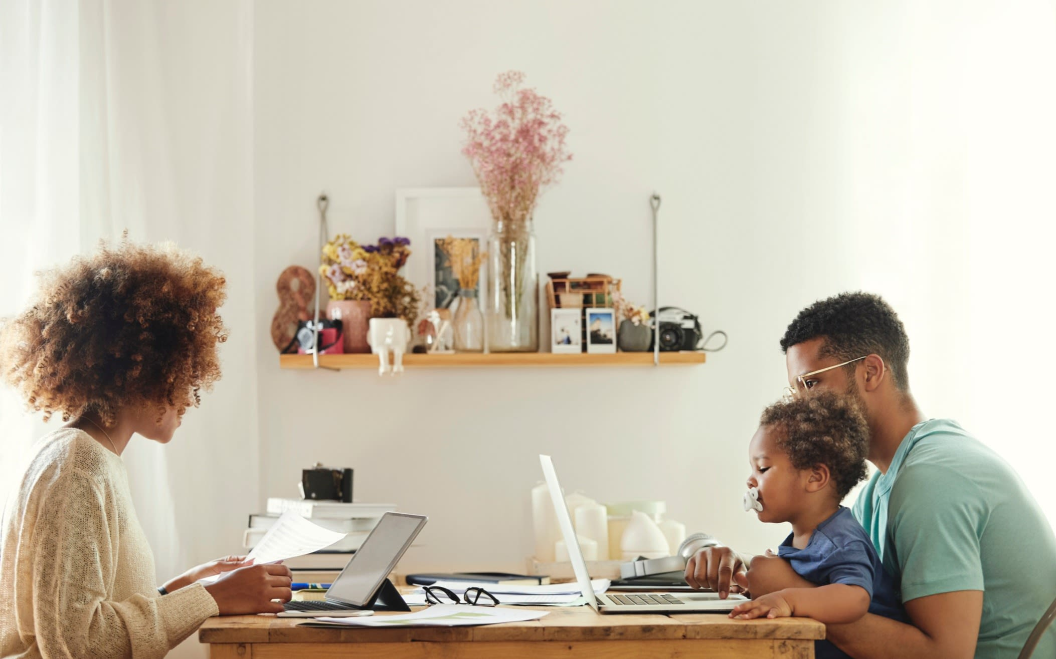 A woman and a man working at a table on laptops. The man has a young child on his lap