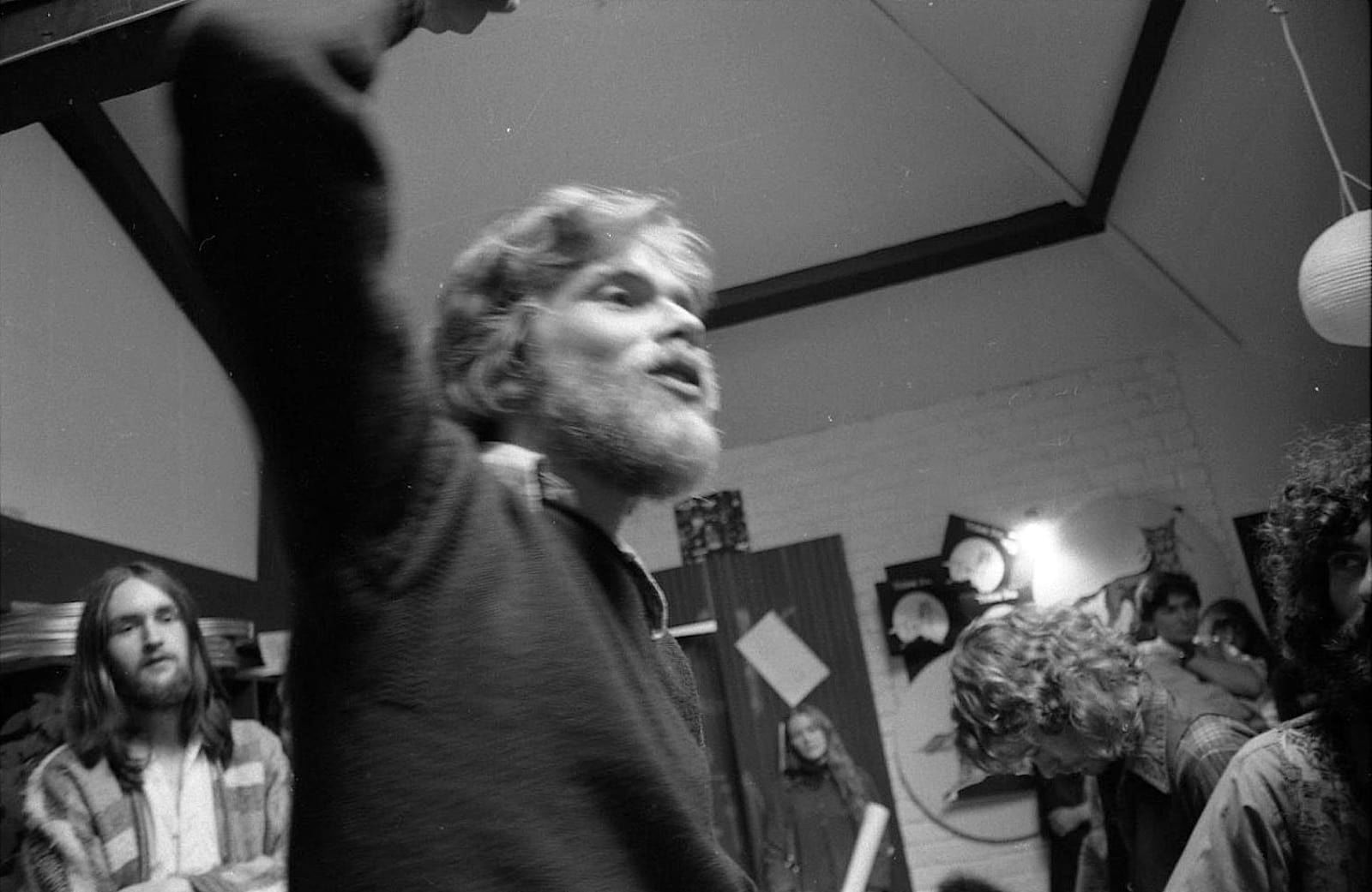 A young, bearded Richard Branson in the studio with his arm raised
