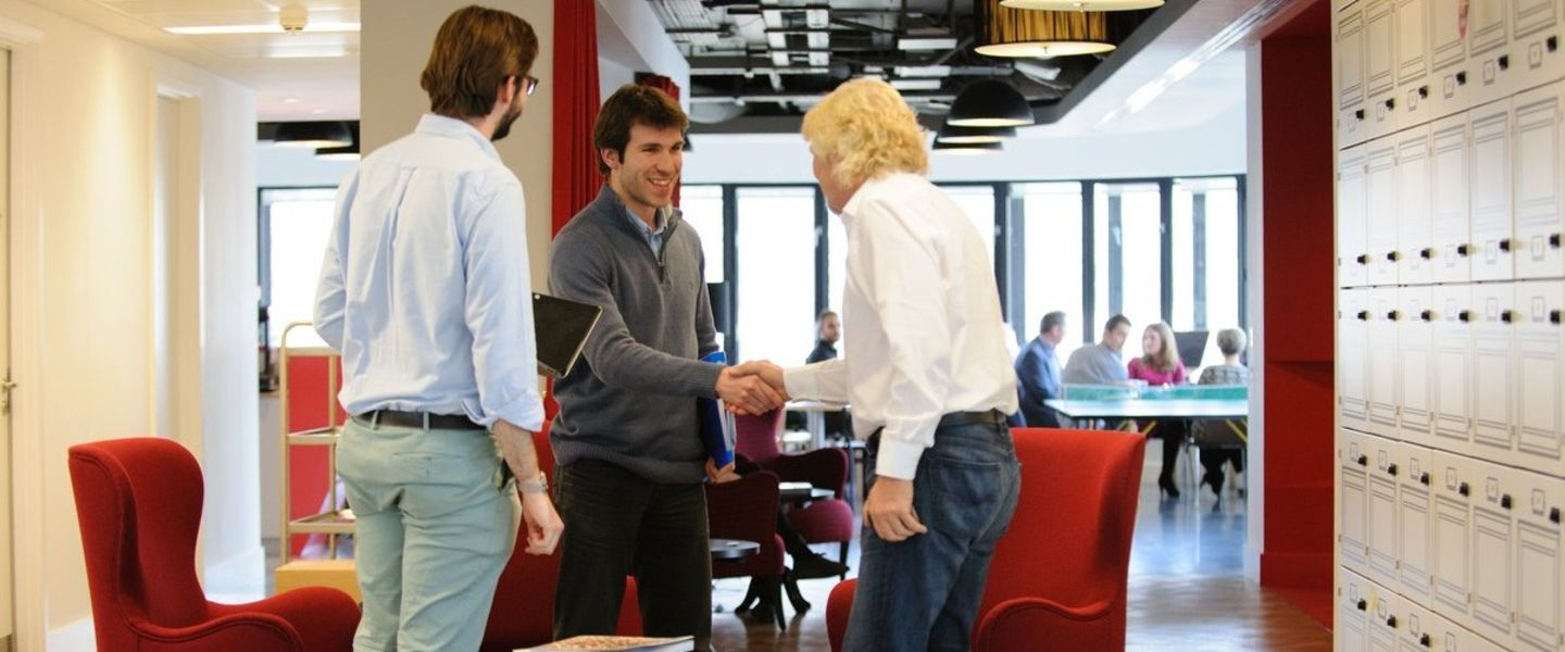Richard Branson shaking hands with employees at the London office