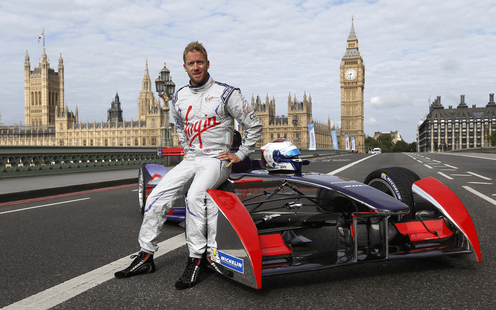 Envision Virgin Racing driver Sam Bird sits on his Formula E car in front of Big Ben and the Palace of Westminster