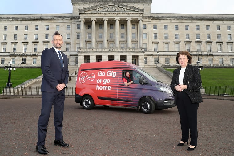 "Seamus McCorry (Virgin Media regional director for Northern Ireland) standing, Paul Murphy (Virgin Media engineer) in a Virgin Media van and economy minister Diane Dodds standing outside Parliament Buildings, Belfast. Text on van reads: ""Go Gig or go home"""
