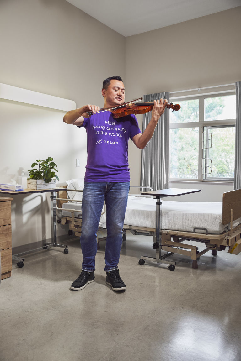 Tom Wu playing the violin in a hospital room
