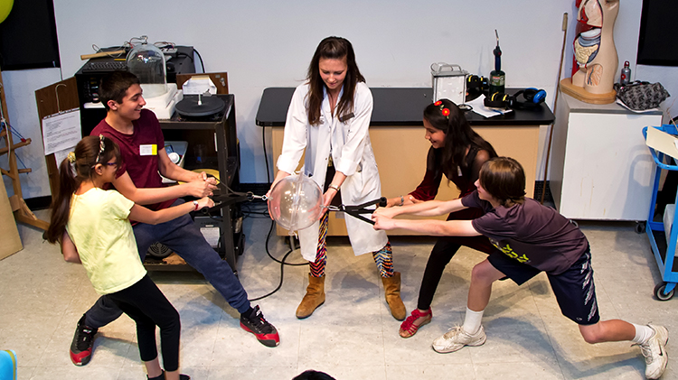 Teacher and kids playing with science teaching aid