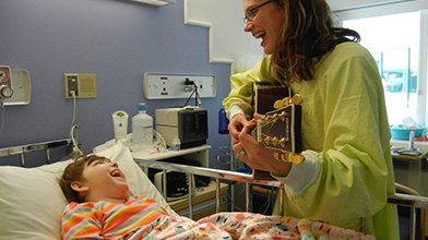 Music therapist playing guitar to sick child