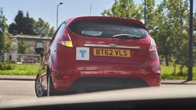 A red Ford fiesta indicating left out of a junction