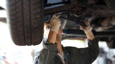 Mechanic working under a lifted car