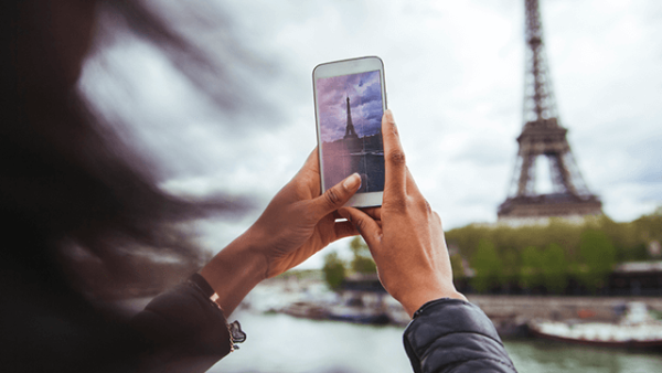 Young woman taking photo of eiffel tower