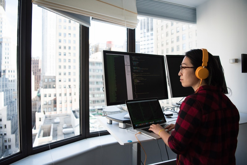 Woman at a standup desk works at a laptop and two additional screens. She