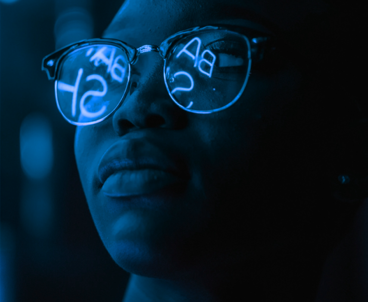 Woman's face with neon text reflecting off her glasses.
