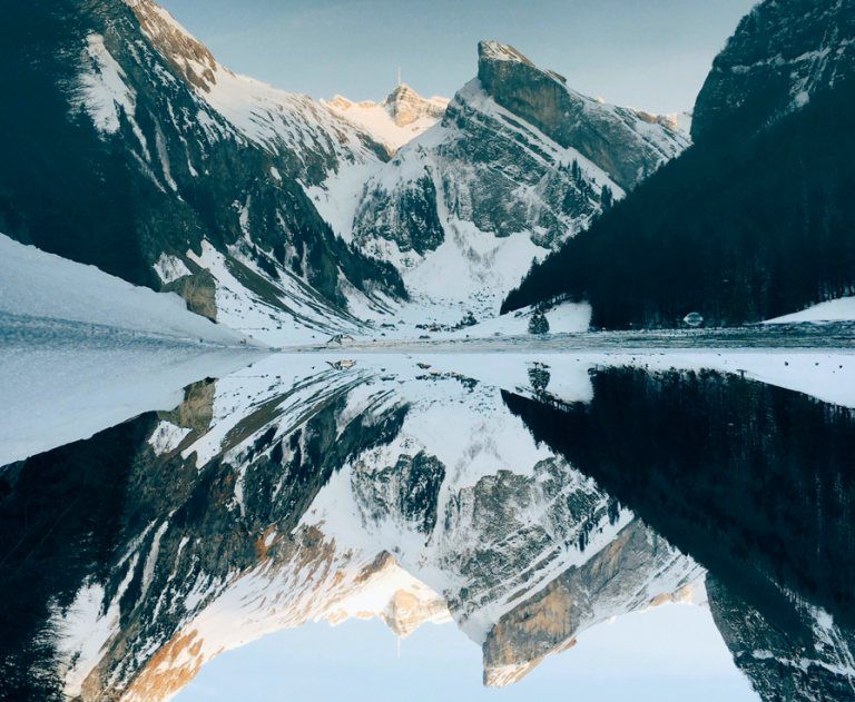 Snow capped mountains with perfect reflection in water below.