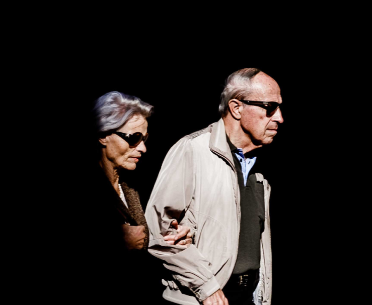 A man and woman, both wearing dark glasses, walking alongside each other, arm in arm.
